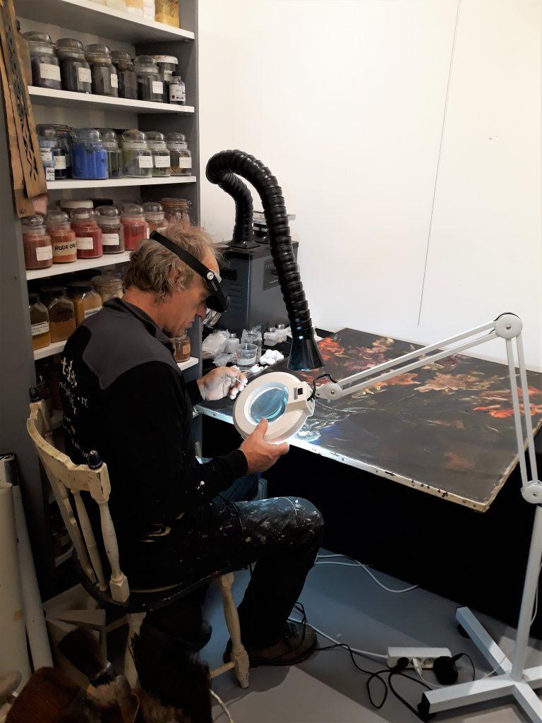Randolph Algera restaureert af en toe live een schilderij in Galerie Autrevue. Moderne middelen in een nostalgisch restauratie atelier.