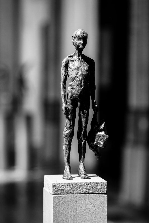 Grootbrengen - bronzen beeld van een naakte jongen met een vogel, gemaakt door Heleen Kater.