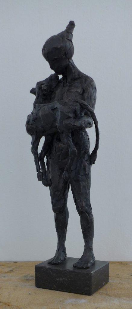 Vrouw die een kalfje draagt in haar armen. Bronzen beeld genaamd 'Koesteren' gemaakt door Heleen Kater.