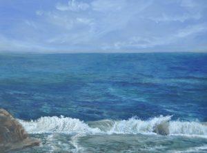 Golven uit de branding breken op de voorgrond. Tot aan de horizon is de oceaan te zien. Het blauw van de zee lost op in het blauw van de lucht.