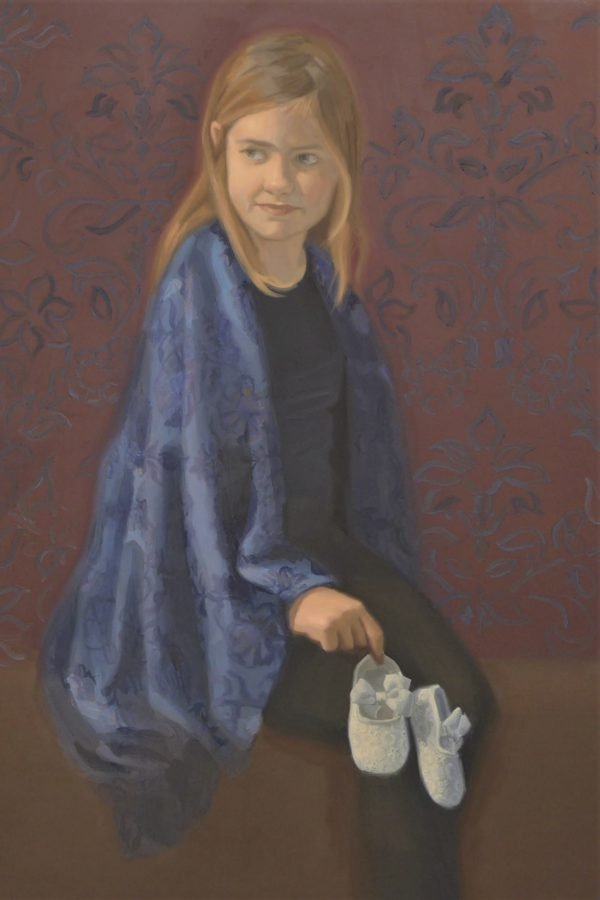 A young girl with long dark blond hair in a blue dress with blue shawl is holding white baby shoes in her hand.