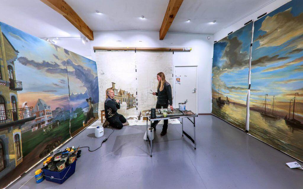 Gabriëlle Westra en Randolph Algera bezig met het schilderen van de muurschildering in hun galerie voor een hotel/grand café in monumentaal pand in Leeuwarden.