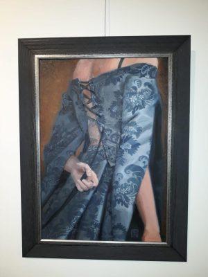 Een vrouw maakt zich klaar voor de nacht. Ze maakt de vetersluiting van haar prachtige blauwe jurk los. Je ziet haar op de rug.