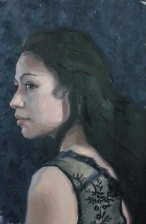 A portrait of a beautifull dark haired woman in a top of translucent fabric.